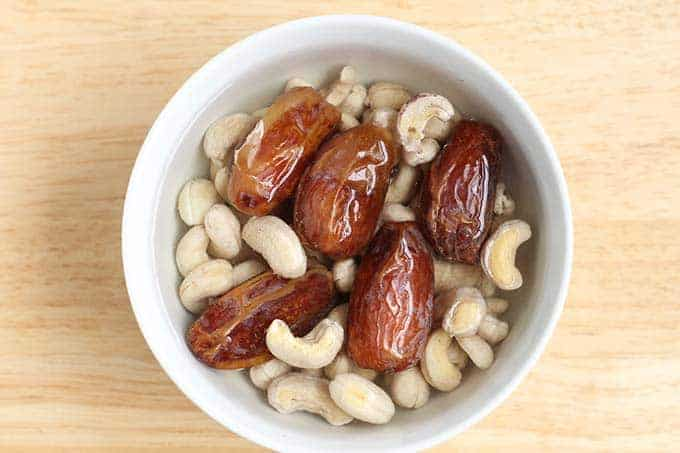 dates and cashews soaking in white bowl