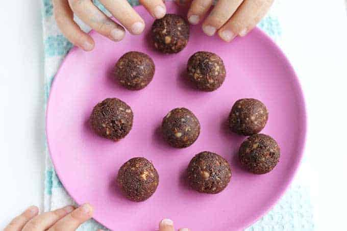 no bake cashew cookies on pink plate with kids hands