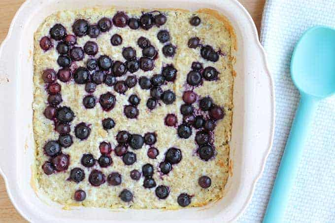 baked oatmeal with blueberries in baking dish with blue spoon