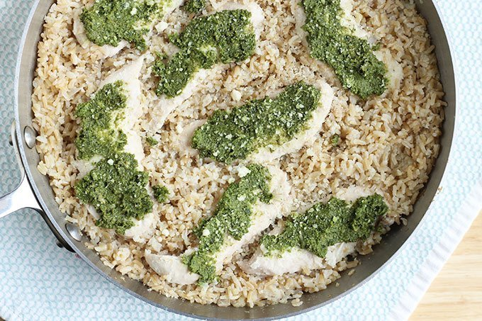 chicken and brown rice in skillet with pesto