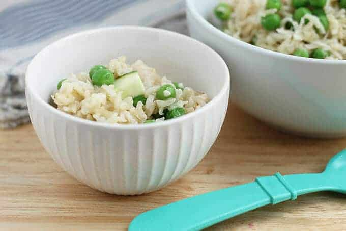 baked brown rice risotto with zucchini and peas in white bowls