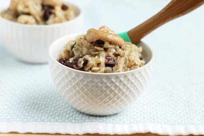 apple oatmeal with raisins in white bowl with spoon