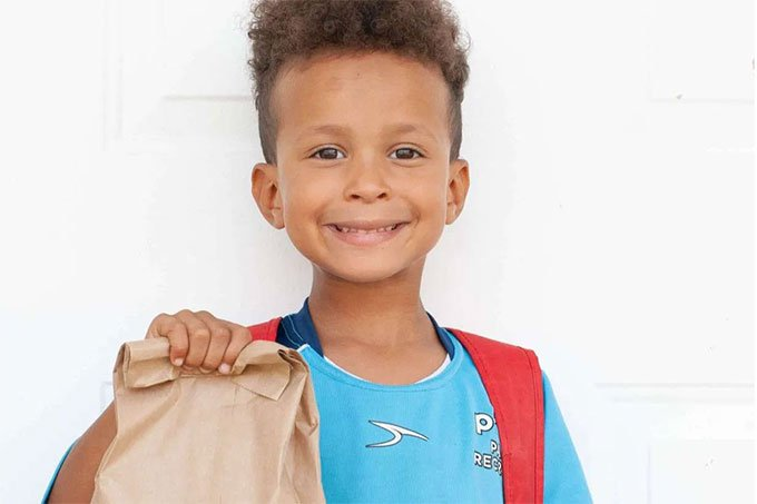 kid holding brown paper lunch bag