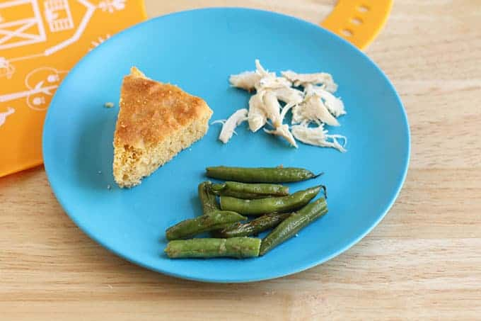 toddler dinner with sesame green beans, corn bread, chicken on blue plate