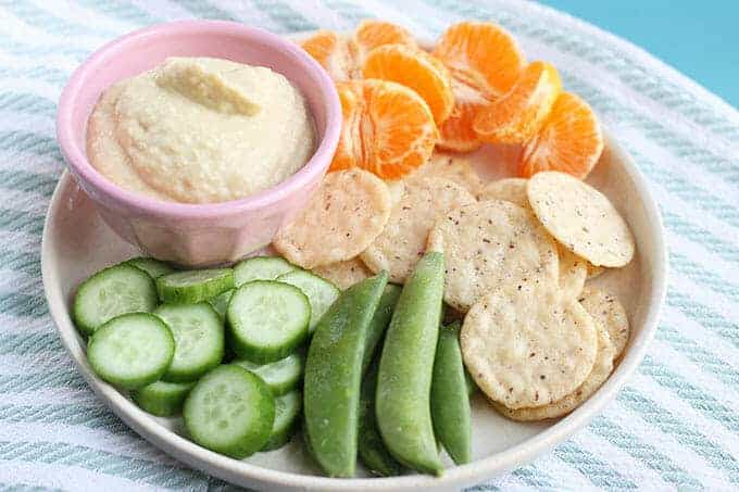 hummus without tahini in pink bowl on plate with vegetables and crackers