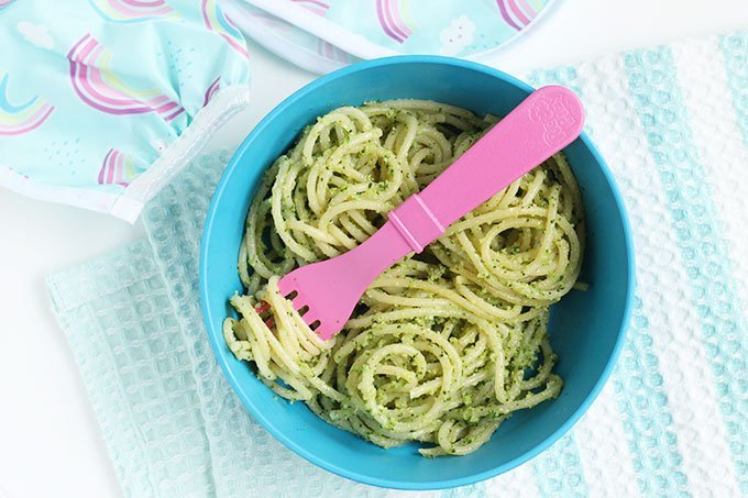 broccoli pesto on spaghetti in blue bowl with pink fork