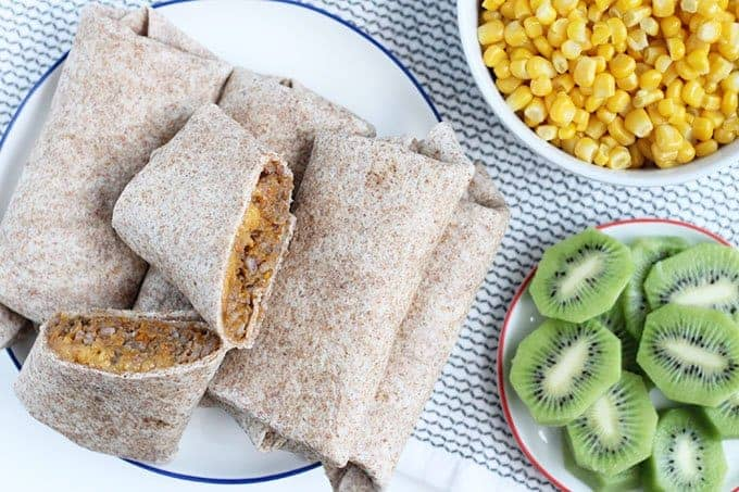 beef burritos cut on plate with corn and kiwi