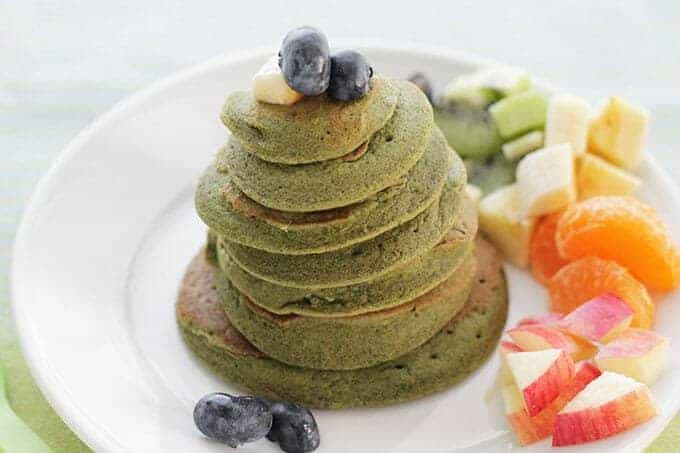 spinach pancake stack with rainbow fruit assortment