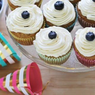 banana cupcakes on cake stand with first birthday hats