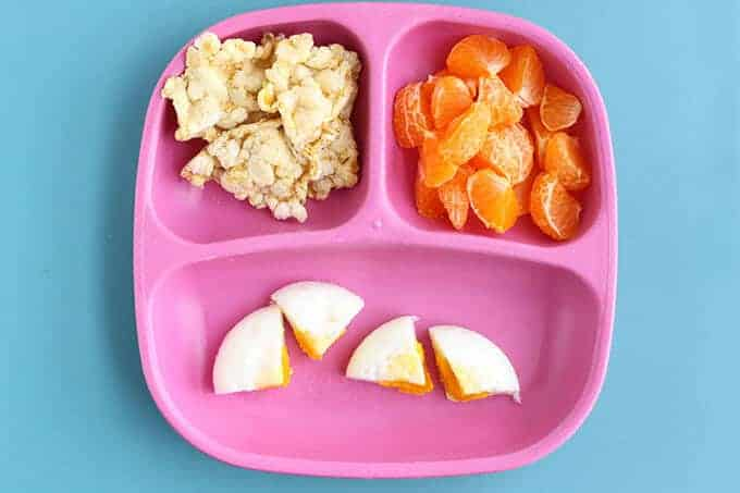 toddler breakfast idea eggs and fruit on pink plate with rice cakes