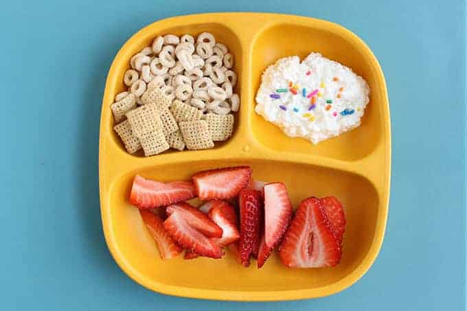 yellow kids breakfast plate with cereal, cottage cheese, and strawberries