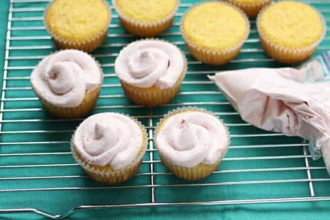 vanilla cupcakes with strawberry frosting in a piping bag on a wire rack
