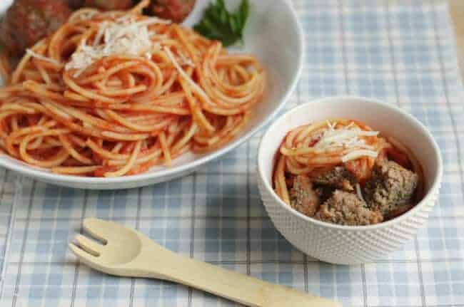 healthy meatballs and spaghetti in white plate and bowl on blue tablecloth