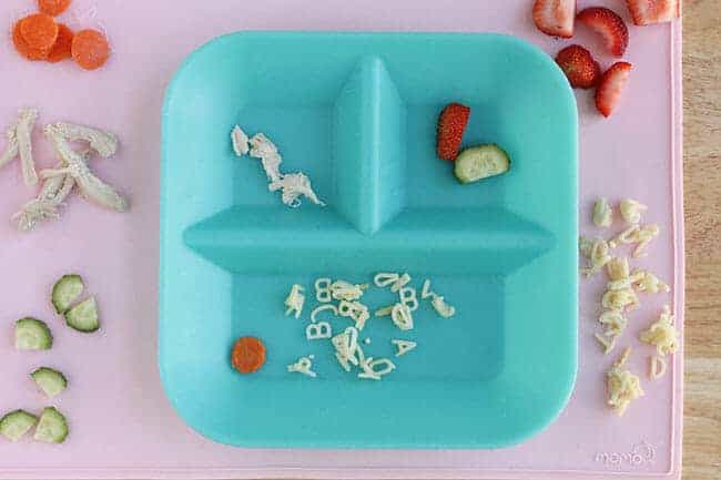blue silicone plate with remains of kids dinner on pink placemat