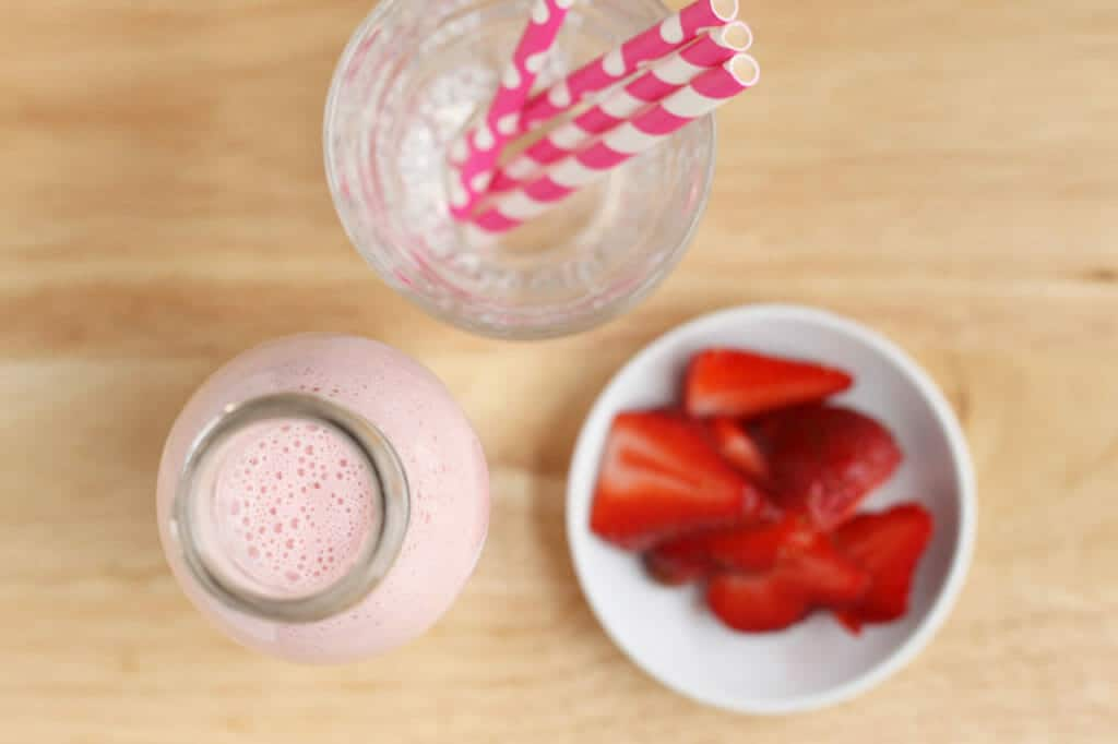 strawberry smoothie recipe with yogurt in bottle with cup of straws and berries