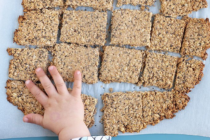homemade granola bars on parchment with toddler hand