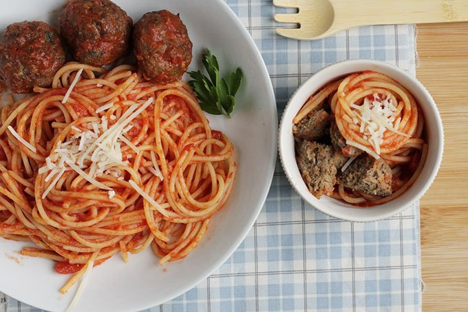 healthy meatballs with spaghetti in white bowls