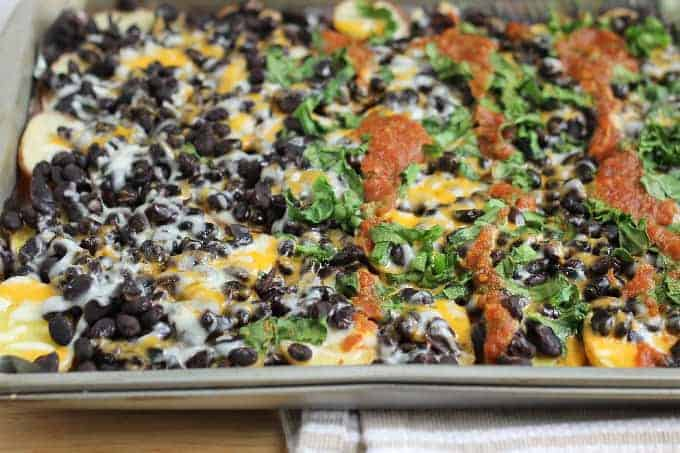 baked healthy nachos on sheet pan with beans and cheese