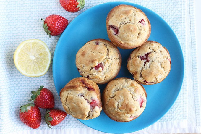 strawberry muffins on blue plate with fresh berries and lemon half