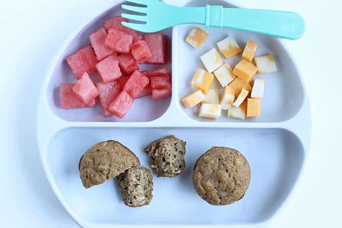 applesauce muffins on white divided plate with fruit and cheese