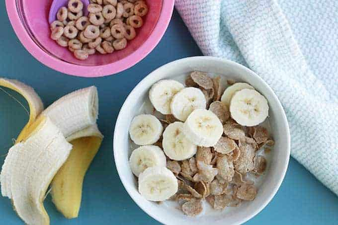 whole grain cereal with banana in bowl on blue background with half banana