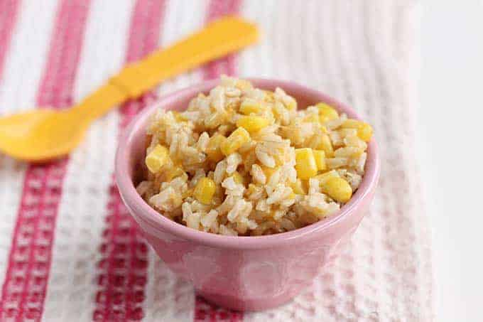 cheesy rice with corn in pink bowl on pink striped tea towel