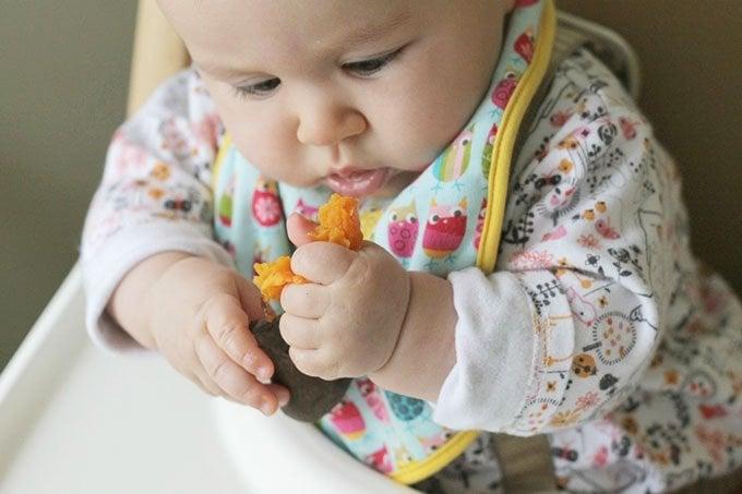 baby eating sweet potato wedge blw