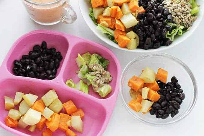 taco salad for kids on pink plate with black beans, romaine, sweet potatoes