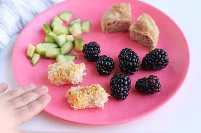 chicken nugget toddler dinner on pink plate with blackberries