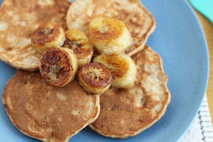 banana oatmeal pancakes with bananas on blue plate
