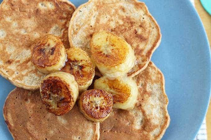 caramelized bananas on pancakes on blue plate