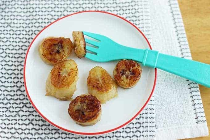 caramelized bananas on white plate with green fork