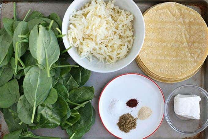 ingredients in spinach quesadillas including baby spinach, cheese, and tortillas
