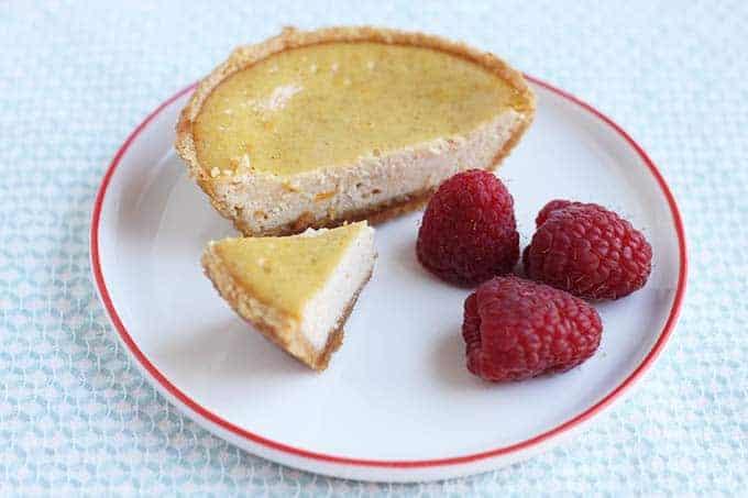 mini ricotta cheesecake sliced with raspberries on a white plate on tea towel