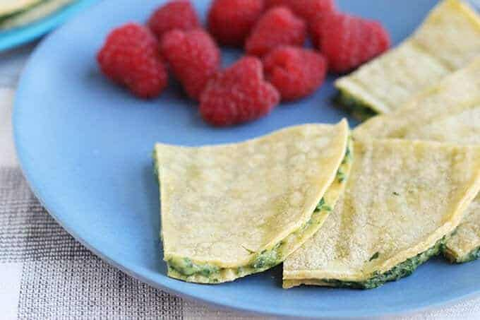 spinach quesadillas on blue plate with raspberries