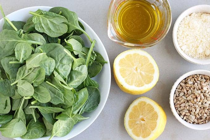 ingredients in spinach pesto with spinach, lemon, olive oil, sunflower seeds