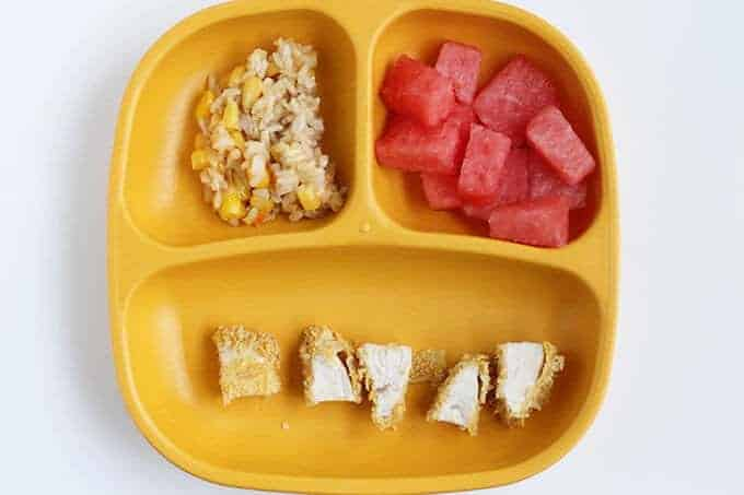 toddler plate of dinner with chicken, cheesy rice and watermelon