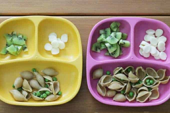 two toddler plates with dinner of pasta with peas, kiwi, and cheese