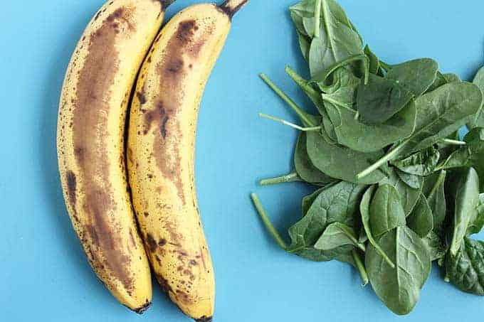 ripe bananas and spinach on blue background
