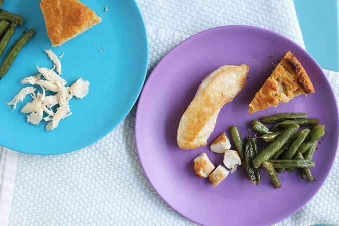 healthy pan-seared chicken on kids plates with green beans and bread