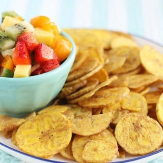 fruit salsa in blue bowl with plantain chips on plate