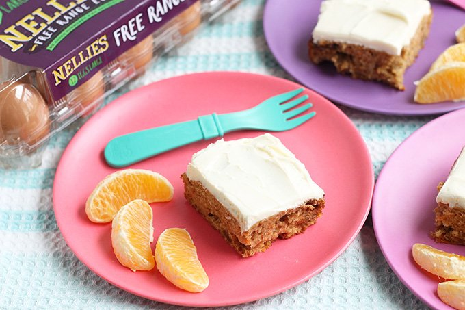 carrot cake bars with oranges on pink and purple plates