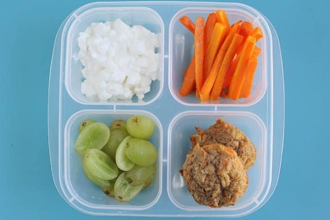 lunchbox with roasted carrots, muffins, cottage cheese, and grapes
