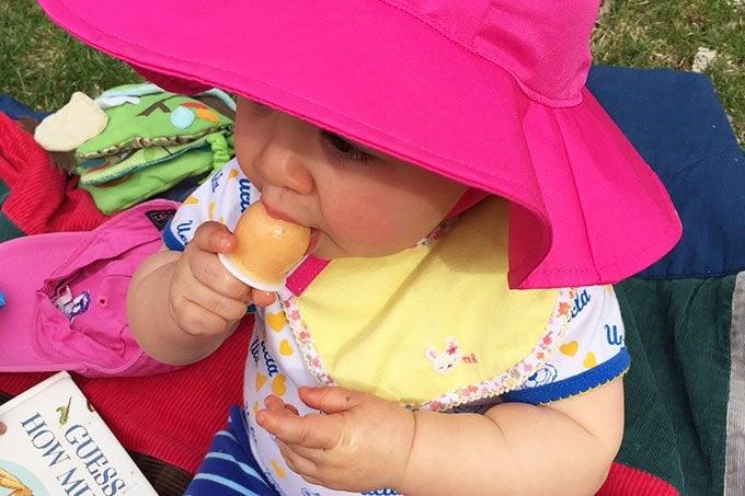 baby eating mango popsicle