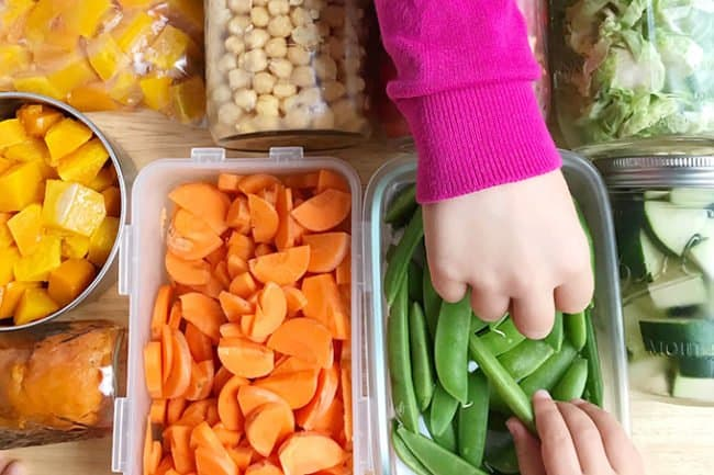 meal prepped veggies with kids hands