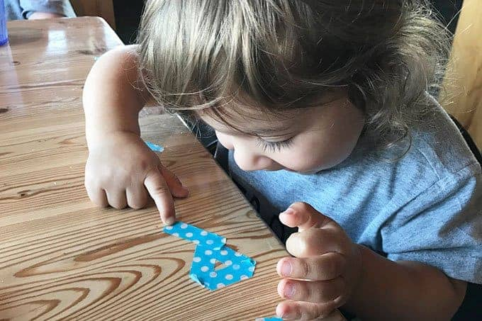 toddler with washi tape in restaurant