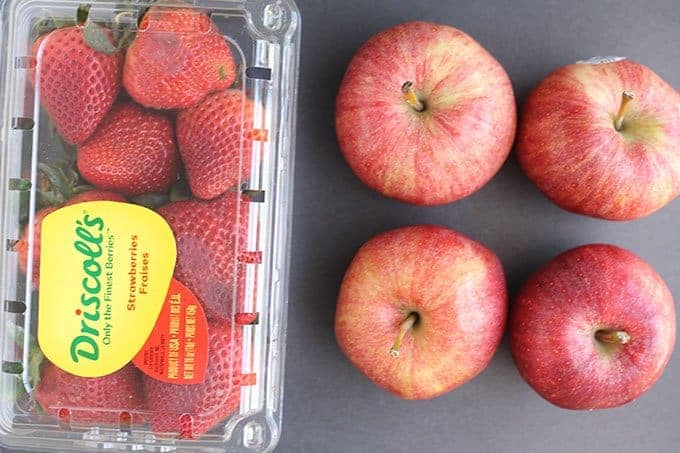 strawberries in container and 4 apples