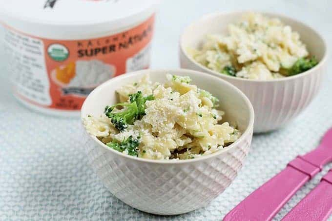 two white bowls of broccoli pasta with cottage cheese