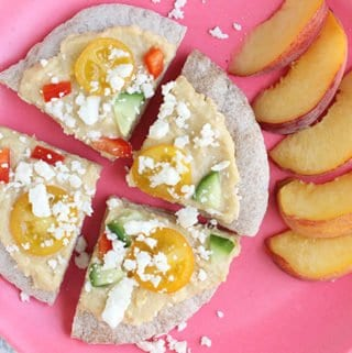greek pita pizzas on pink plate with peaches