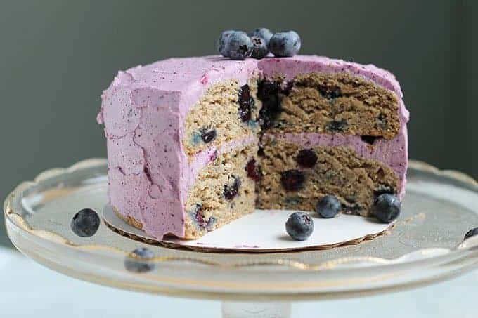 sliced first birthday cake with blueberries on stand